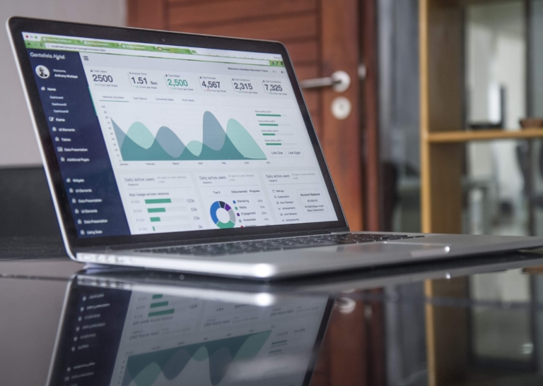 A laptop shows graphs and data about a project