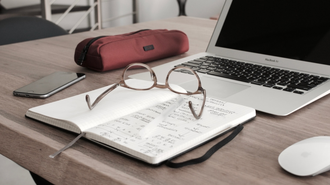 An image of a notebook with budgeting information set in front of a laptop. Glasses rest atop the notebook.