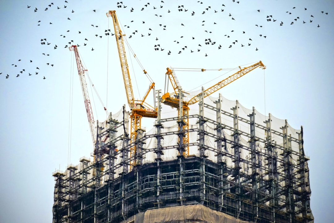 Image of a building being assembled by a series of cranes.