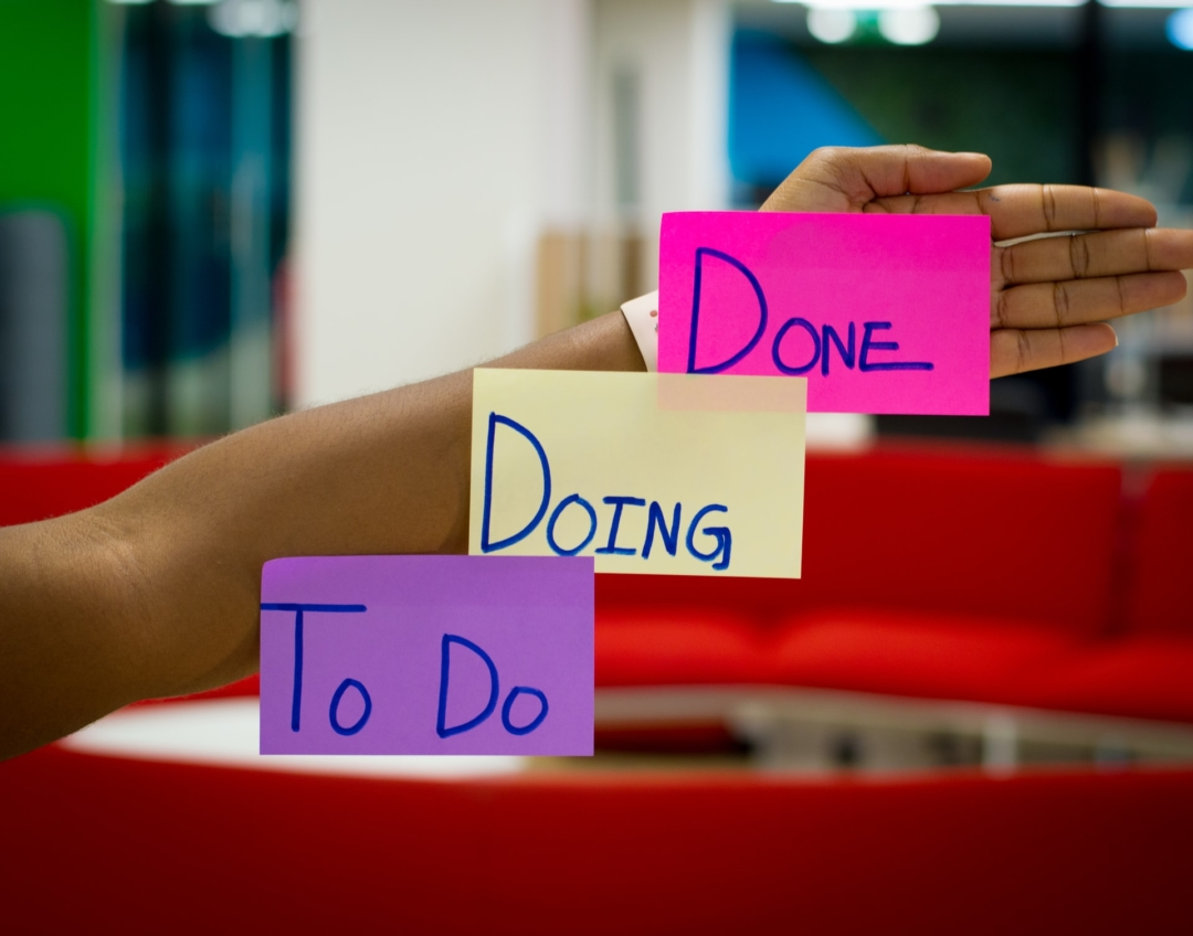 Image of a woman's arm extended, with three sticky notes reading, in order, 'To Do', 'Doing', and 'Done.'